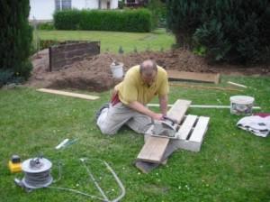 Bretter werden für das Fundament auf Länge geschnitten
