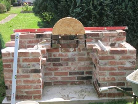 Gartengrillkamin selber gemauert und Holz für den Rundbogen verkeilt